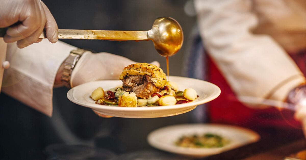 Der Gourmet-Teller mit überbackenem Rinderfilet, selbst gemachten Gnocchi und Bohnen-Allerlei wird perfekt angerichtet.