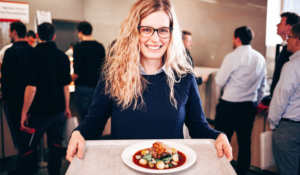 Eine fischer Mitarbeiterin präsentiert stolz das leckere Essen aus dem Betriebsrestaurant.
