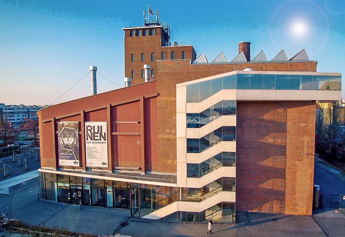 KINDL – Zentrum für zeitgenössische Kunst, Berlin: Blick auf das scheinbar schwebende Treppenhaus aus Glas und Sichtbeton.