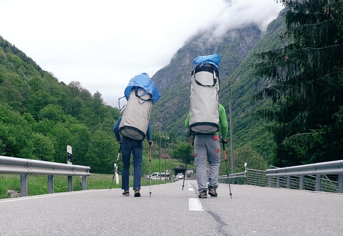 Zwei Kletterer schleppen riesige Transportrucksäcke zum Poncione d'Alnasca.