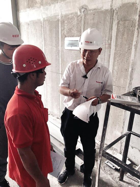 fischer Mitarbeiter Yafeng Zhang im Gespräch mit Bauarbeitern.