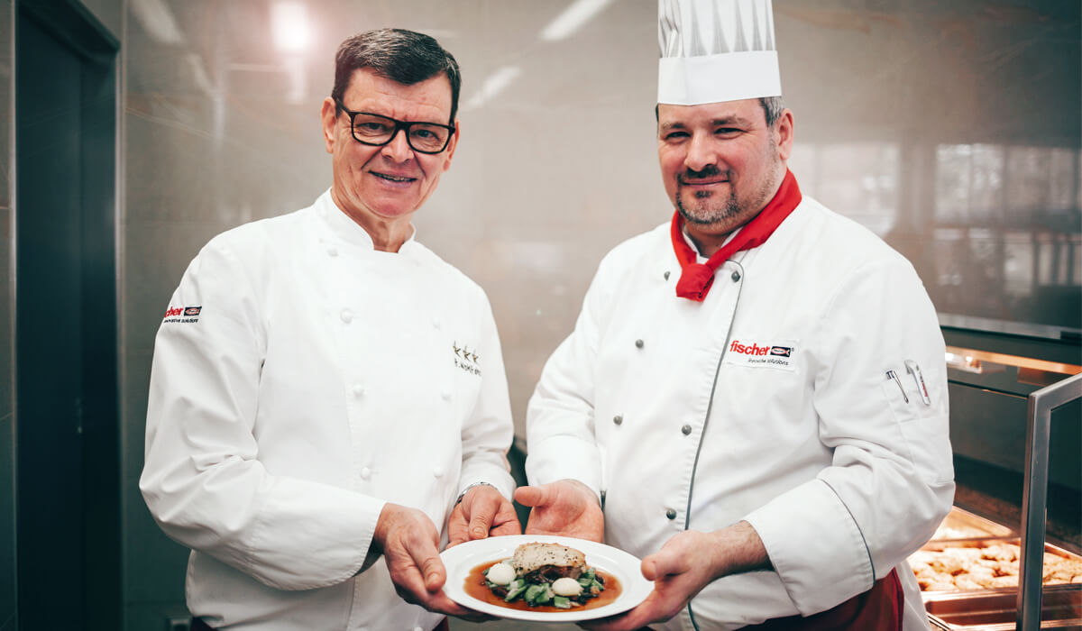 Koch-Legende Harald Wohlfahrt (links) kocht zusammen mit dem Küchenchef Franky Gissinger im Betriebsrestaurant von fischer.