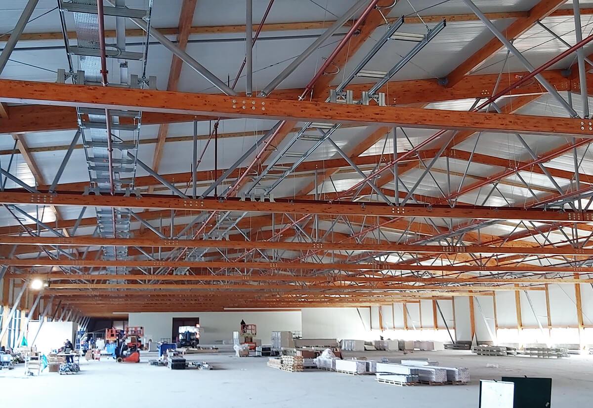 Eine 250 Meter lange, 50 Meter breite Fabrikhalle, überspannt von einer Holz-Stahl-Konstruktion. Ein BIM-Modell ermöglichte die einfache Installation von Lüftungstechnik.