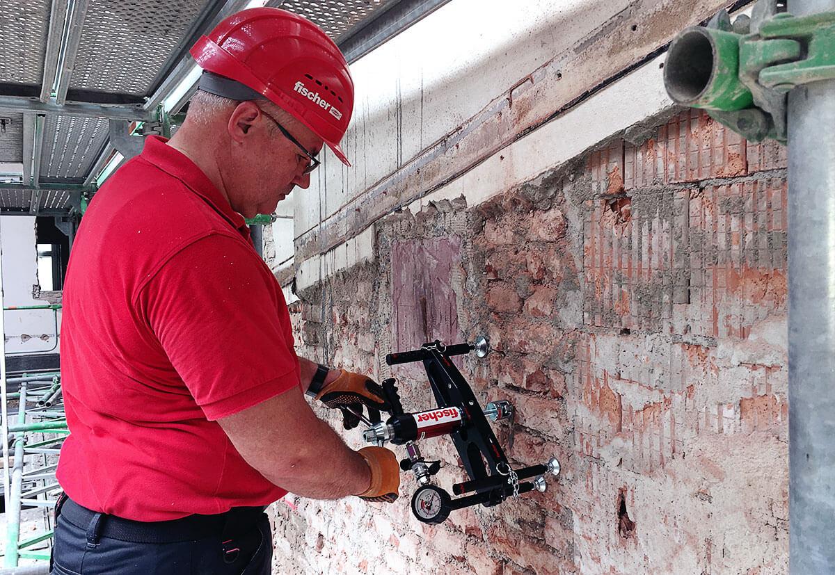 Ein Anwendungstechniker von fischer bei der Bestimmung der Dübeltragfähigkeit durch Zugversuche an einem Bauwerk.