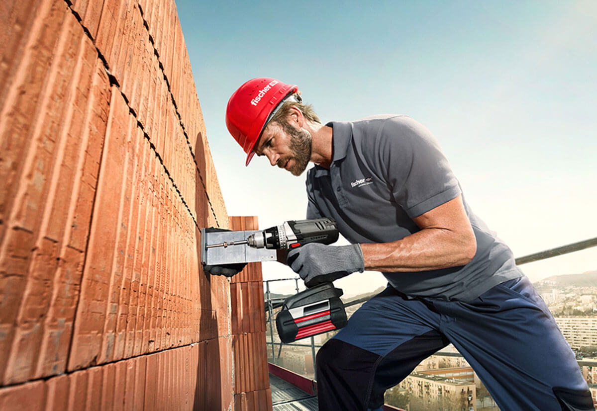 Ein Handwerker trifft auf einer Baustelle mithilfe von Injektionsmörtel Vorkehrungen für die Befestigung schwerer Lasten auf einem Mauerwerks-Untergrund.