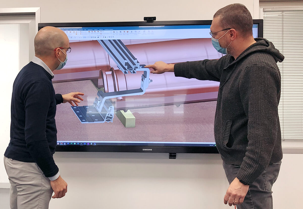 Developers observing a fastening solution simulation on a screen.